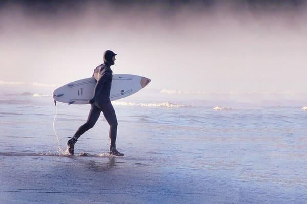 冬の海。完全防備で海に入ろうとするサーファー